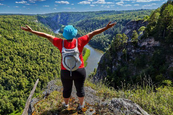 Dame med ryggsekk på toppen av et fjell
