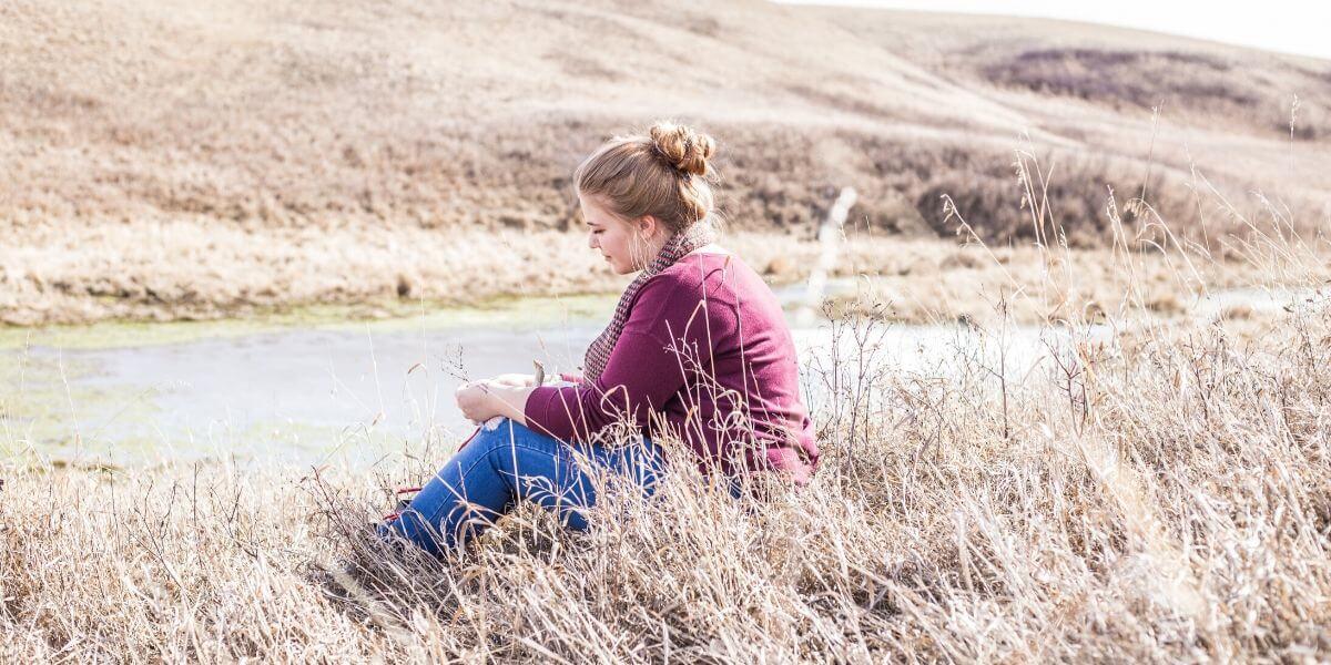 Dame som sitter ved en elv